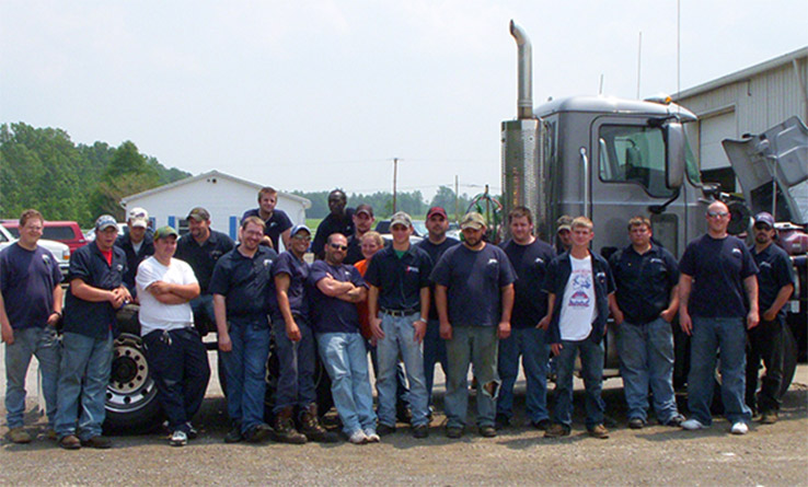 Group of TDDS Technical Institute memembers in front of a truck